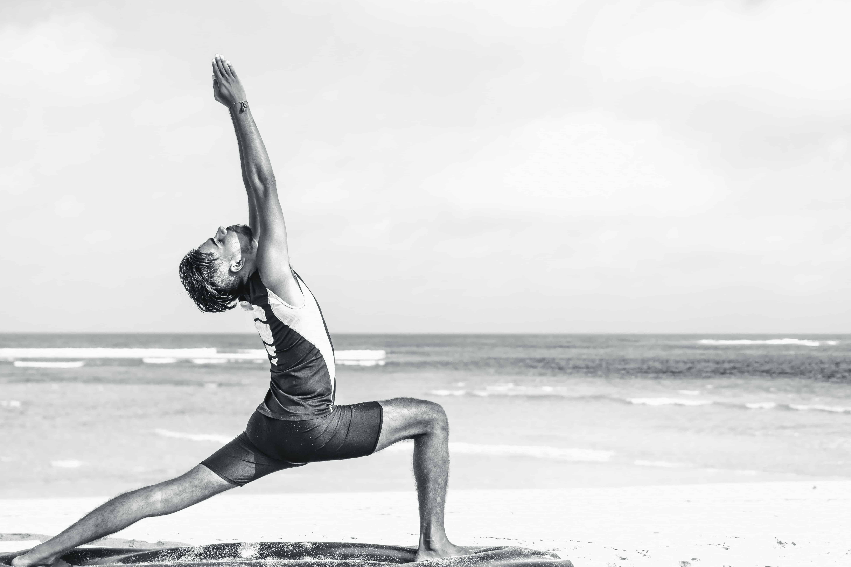 Rechtenvrije foto van een yogameneer op het strand door Artem Bali via Unsplash