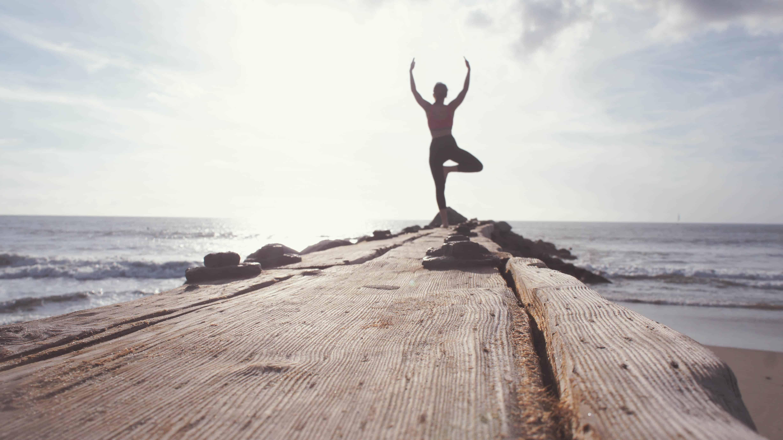 Rechtenvrije foto van een yogapose op een pier van Marion Michele via Unsplash